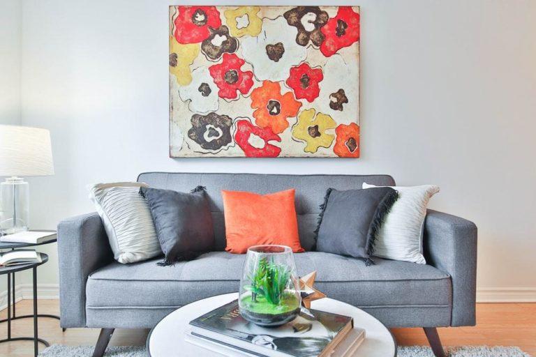 Description: throw pillows on cushioned sofa by wall