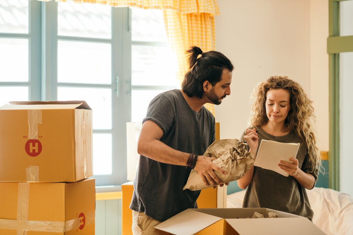 Cheerful young man and woman smiling while unpacking carton boxes with belongings in new apartment during relocation and looking at paper